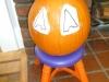 Apply each cut out design element to the pumpkin.