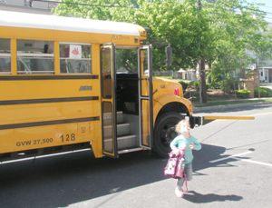 child-getting-off-yellow-school-bus